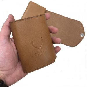 odinė šviesiai rudos spalvos vyriška piniginė rankoje