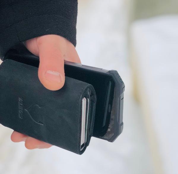 juoda odinė piniginė rankoje