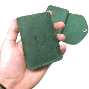 žalia odinė vyriška piniginė laikoma rankoje